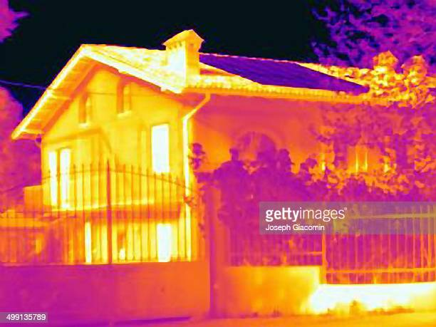 Thermal image of a house with solar cells on the roof. Absorbing the light energy, the solar panel on roof appears cold in the image