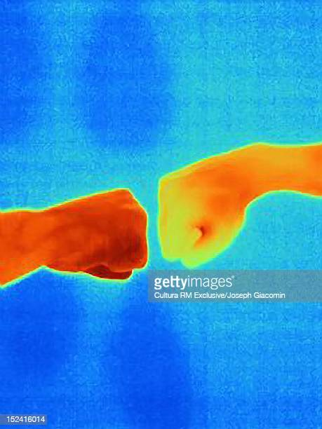 Thermal image of hands bumping