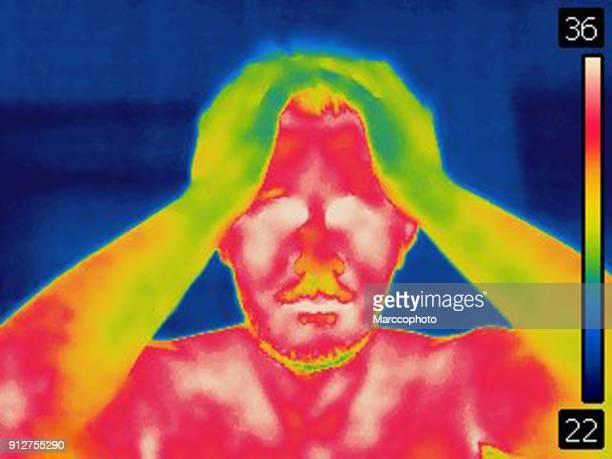 immagine termica dell'uomo che tiene la testa con le braccia - infrarosso foto e immagini stock