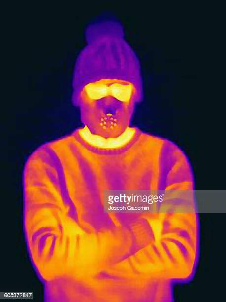thermal image of man with crossed arms wearing threatening mask and knit hat - infrarosso foto e immagini stock