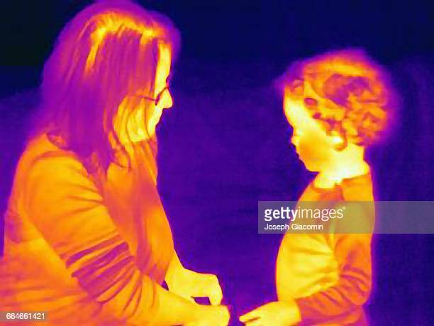 Thermal image of mature woman and son face to face