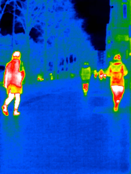 Thermal image of unrecognizables persons walking in a street with trees. Berlin. Germany.
