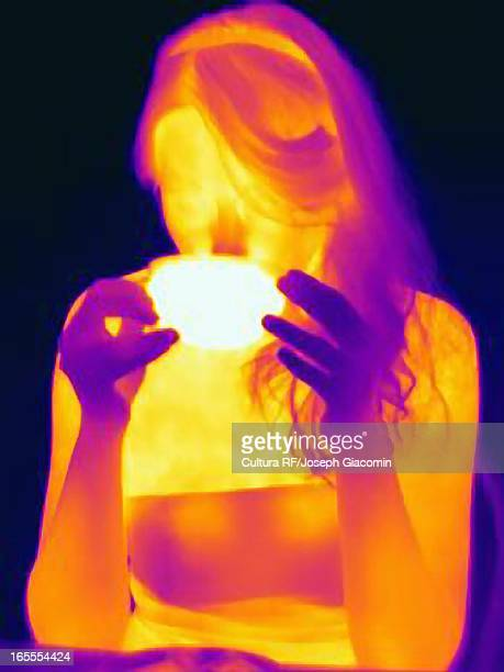 Thermal image of woman having cup of tea