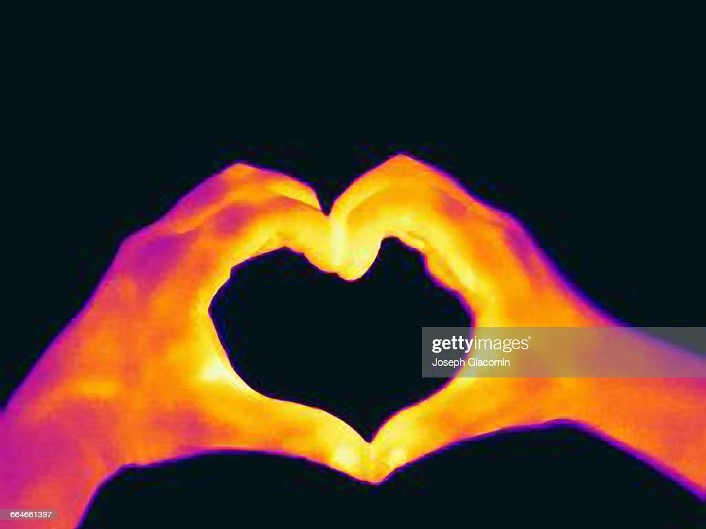 Thermal image of womans hands making a heart shape : Stock Photo