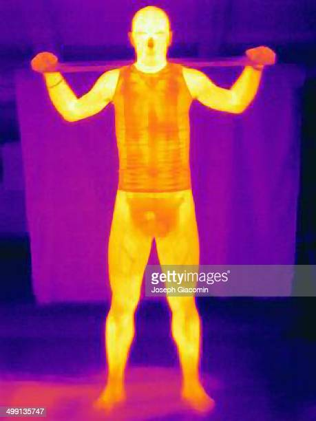 Thermal image of young man training with a metal bar