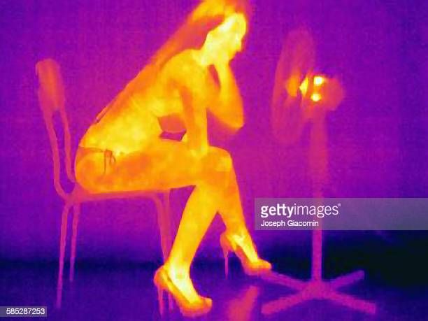 Thermal image of young woman, partially clothed, sitting on chair in front of fan
