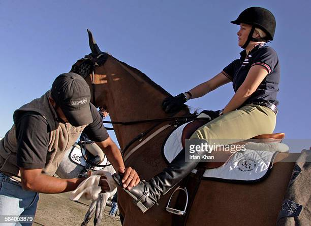 Thermal Mar02 2007 A stable hand Juan Contreras left wipes boots of Jessica Helm as she saddles for a jump in equestrian event going on in Thermal...