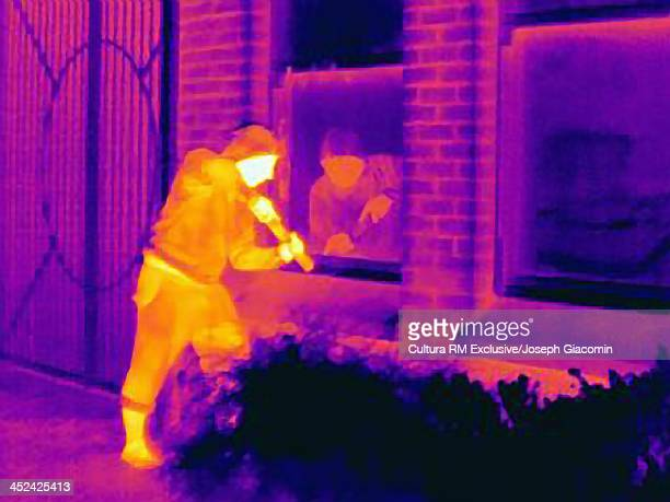 Thermal photograph of a burglar breaking into a house
