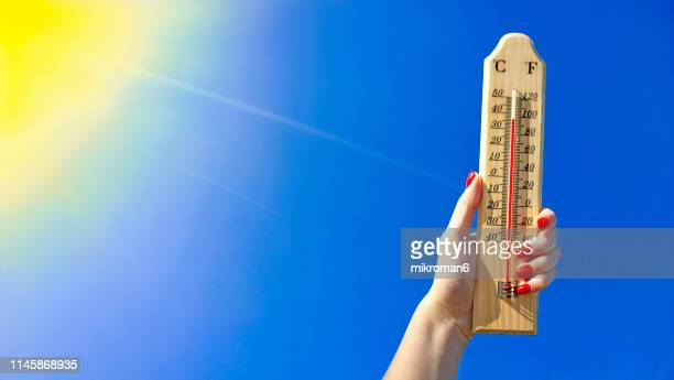 thermometer against a bright blue sky - heat wave stock pictures, royalty-free photos & images