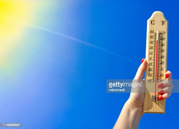 thermometer against a bright blue sky - glödande bildbanksfoton och bilder
