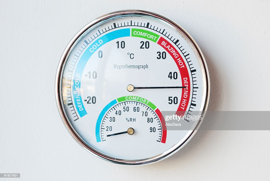 Thermometer hanging on a wall showing a high temperature : Stock Photo