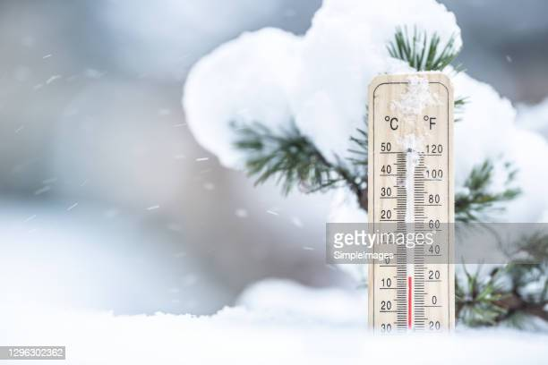 thermometer in the snow shows low temperatures in celsius and farenhaits. - cold temperature stock pictures, royalty-free photos & images