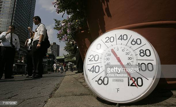 A thermometer in the sun on the sidewalk indicates a temperature of 120 degrees Fahrenheit as people eat ice cream on the Upper West Side August 2...