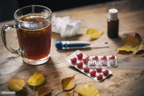 Thermometer, medicine, tissue and a cup of tea on wooden background