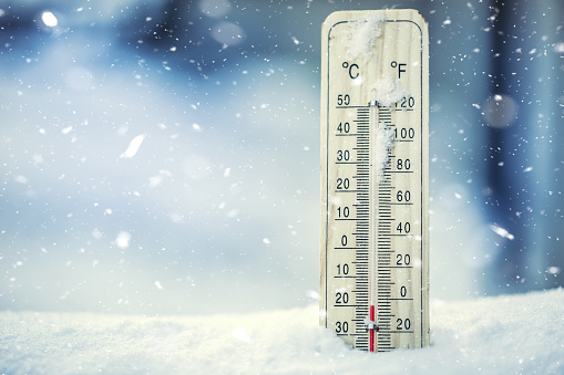 Thermometer on snow shows low temperatures under zero. 637409946