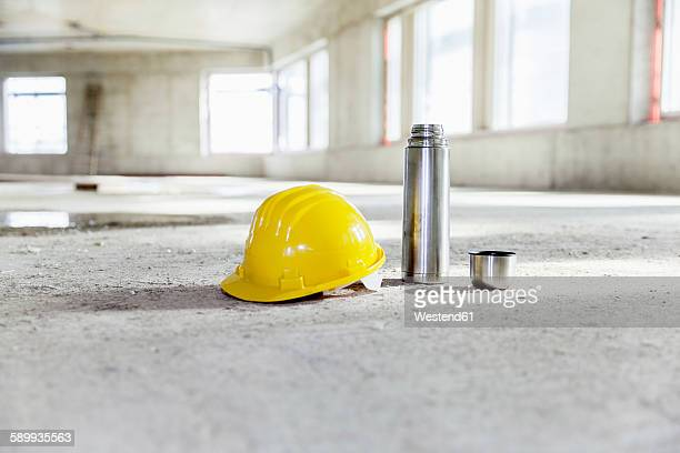 Thermos flask and hard hat on concrete floor on construction site