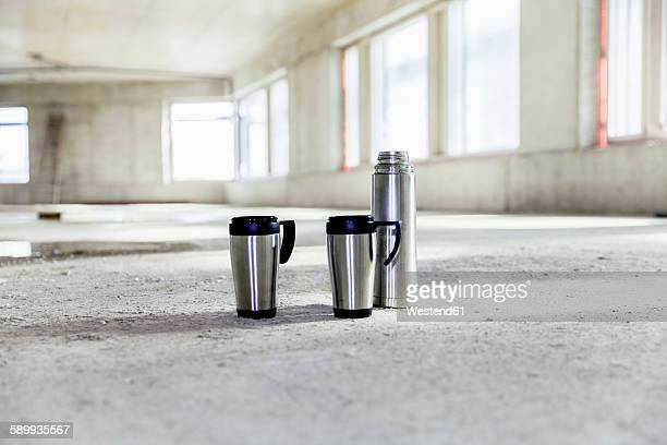 Thermos flask and mugs on concrete floor on construction site