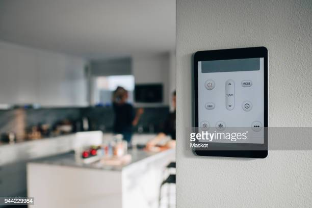 thermostat app on digital tablet mounted over white wall at home - internet delle cose foto e immagini stock
