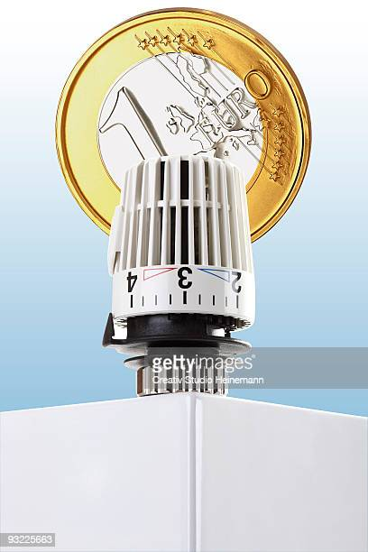 Thermostat on heating and Euro coin, close-up, (digital composite)