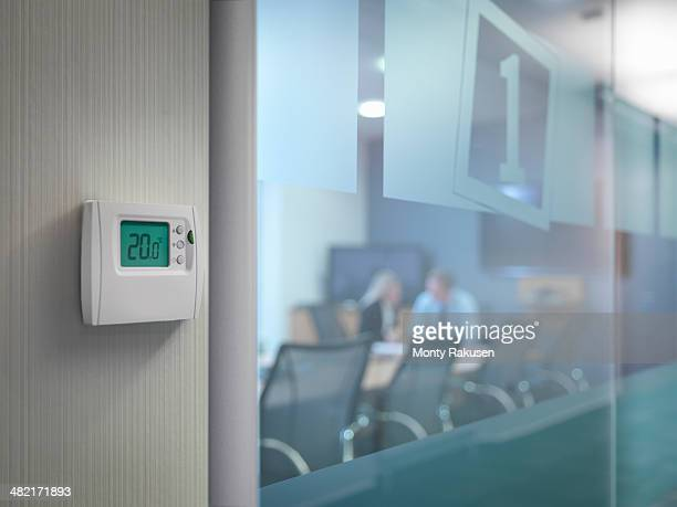 Thermostat outside conference room with office workers in meeting
