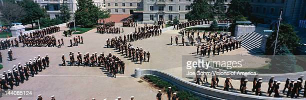 These are students of the United States Naval Academy marching in their noon meal formation They are marching outdoors around a courtyard in their...