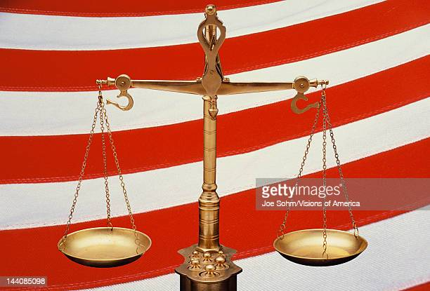 These are the golden Scales of Justice set against a background of the red and white stripes of the American flag The scales are in a balanced...