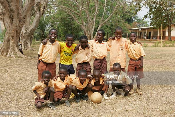 These children, including a Liverpool fan pose for a team photograph during a break from playing soccer during play time at the No.1 School, Enkawaba...