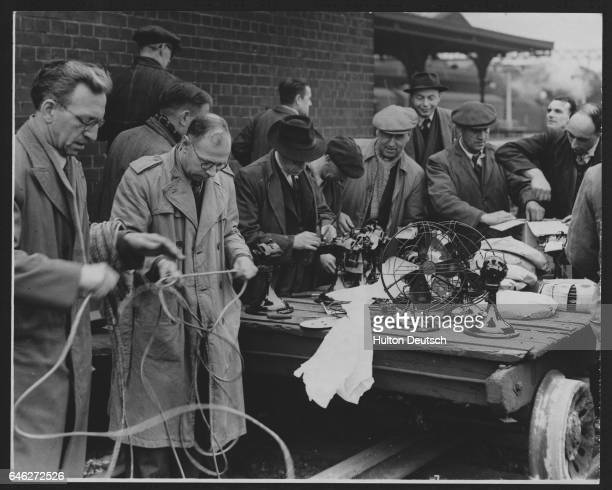 These electricians from the General Electric Company are wiring up fans to clear the smoke and combat the heat from the disaster scene at a tunnel...