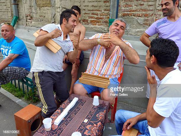 """These gypsies were playing some game on the streetside in Bucharest and I wanted to take a picture as they played the game. The """"boss"""" was very..."""