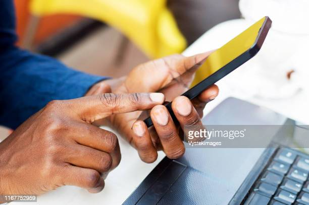these human hands manipulate a mobile phone. - abidjan stock pictures, royalty-free photos & images