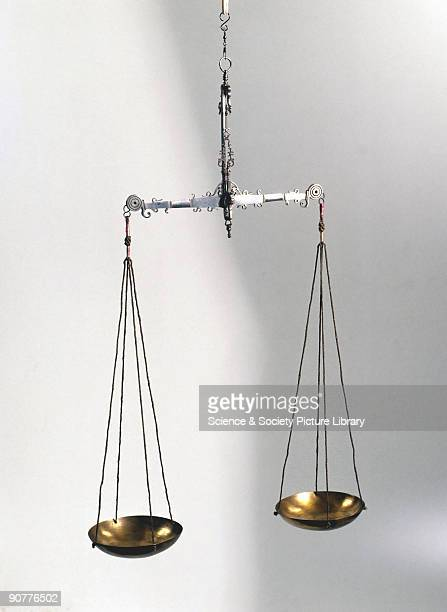 These jeweller's scales have an ornamental polished steel beam and gallows suspension with two brass pans which are supported by woven silvered cords...