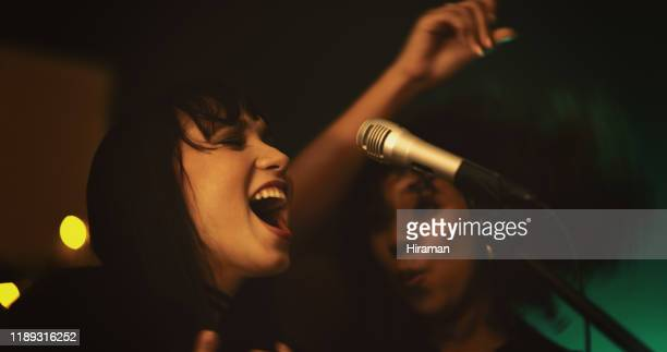 deze dames weten hoe ze het leven aan het feest kunnen brengen - karaoke stockfoto's en -beelden