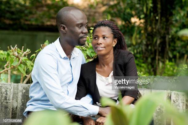 these lovers are taking air, sitting at the park. - femme ivoirienne photos et images de collection