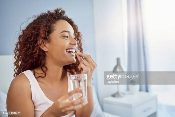 これらのマルチビタミン錠は私の一日を強化するのに役立ちます - 口を使う ストックフォトと画像