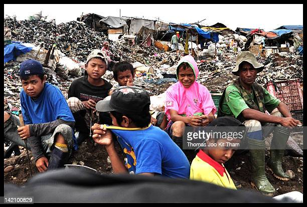These scavengers were waiting for garbage from trucks to be dumped here. There were many children work the site.