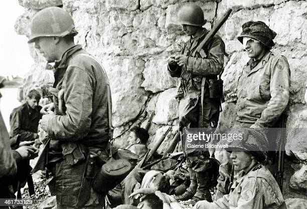 These soldiers from the1st Infantry Division are protected from German fire at the foot of the cliff of CollevillesurMer 6th June 1944 This is the...