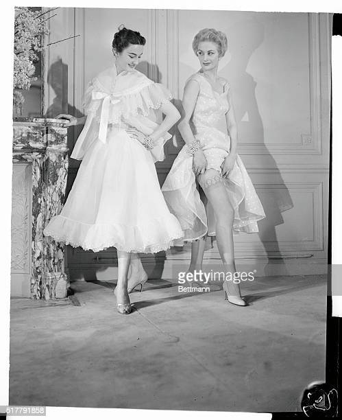 These two models demonstrate the latest styles from the Jacques Fath fashion house They are wearing frills with trim accessories At left is a white...