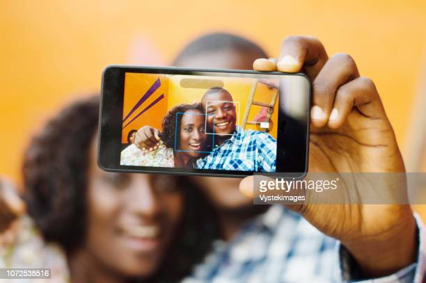 these young people take pictures trough mobile phone - femme ivoirienne photos et images de collection