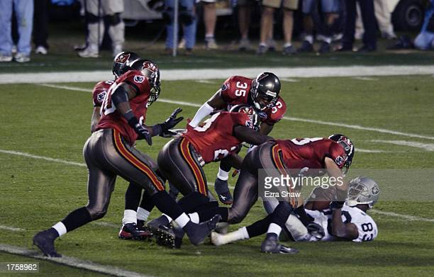 TheTampa Bay Buccaneers defense piles onto Marcus Knight of the Oakland Raiders in the third quarter of Super Bowl XXXVII on January 26 2003 at...