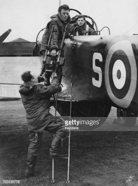 TheTwin Vickers K machine guns are loaded into the radio operators dorsal position section of a Handley Page Hampden twinengine medium bomber of No61...