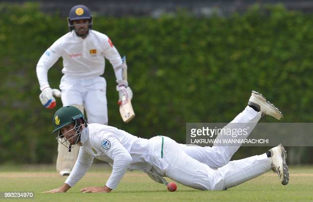 Theunis de Bruyn of South Africa dives as he attempts to field a ball hit by Dhananjaya de Silva of Sri Lanka Board XI during the opening day of a...
