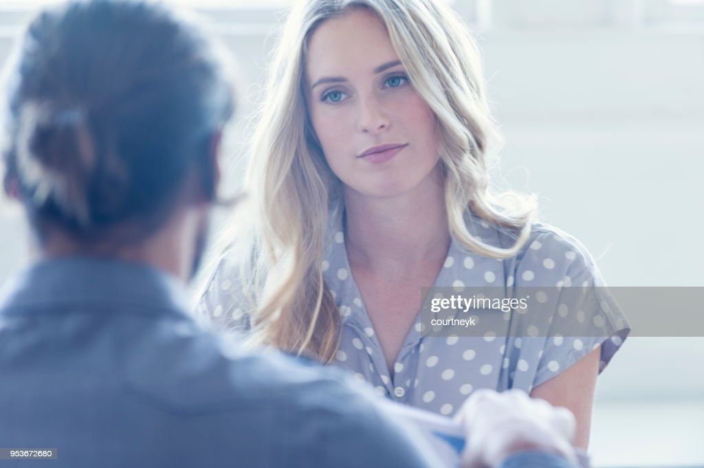 They are both young business people casually dressed in a bright office. : Stock Photo