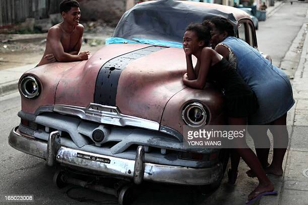They are happy together by the side of an old car in Santiago, CUBA