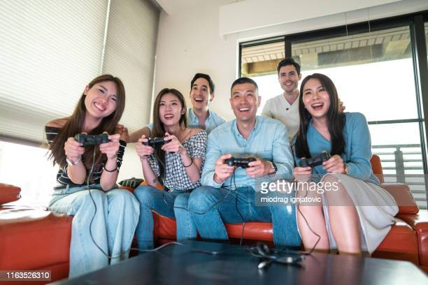 they get so excited when they play games - medium group of people stock pictures, royalty-free photos & images