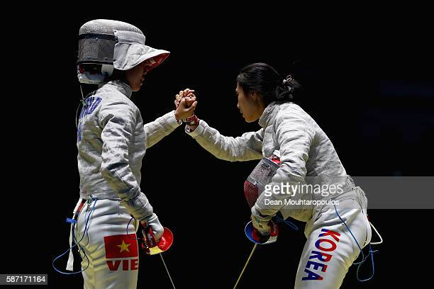 Thi Le Dung Nguyen of Vietnam and Jiyeon Kim of Korea shake hands following the Women's Individual Sabre on Day 3 of the Rio 2016 Olympic Games at...