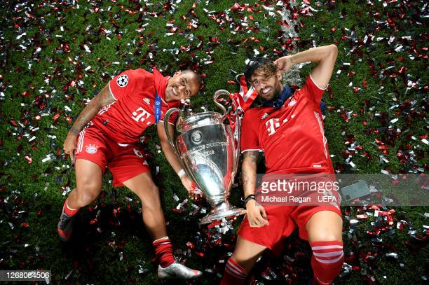 Thiago Alcantara and Javi Martinez of FC Bayern Munich celebrate with the UEFA Champions League Trophy following their team's victory in the UEFA...