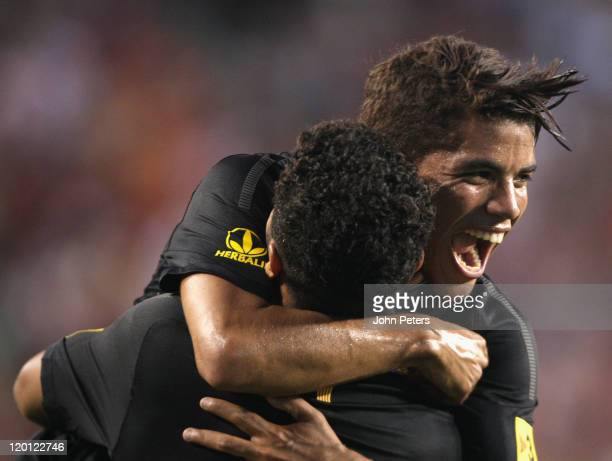 Thiago Alcantara of Barcelona celebrates scoring their first goal with Jonathan dos Santos during the pre-season friendly match between Manchester...