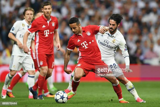Thiago Alcantara of Bayern Muenchen holds off Isco of Real Madrid during the UEFA Champions League Quarter Final second leg match between Real Madrid...