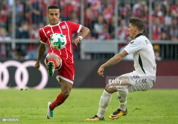Thiago Alcantara of Bayern Muenchen while Mike Frantz of Freiburg looks on during the Bundesliga match between FC Bayern Muenchen and SportClub...