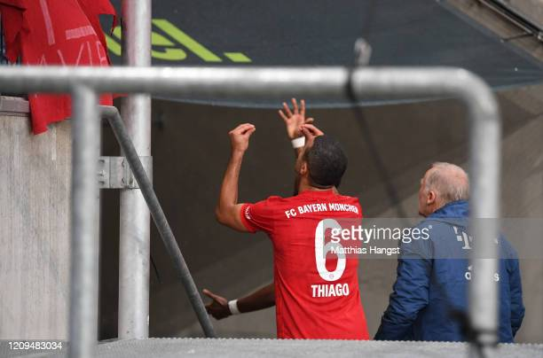 Thiago Alcantara of Bayern Munich and team mates appeal to their fans to remove a banner during the Bundesliga match between TSG 1899 Hoffenheim and...